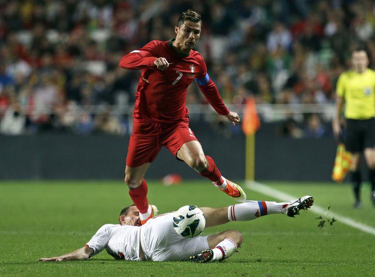 Cristiano Ronaldo ontwijkt een tackle van de Rus Alexei Kozlov tijdens een kwalificatiewedstrijd Beeld ap