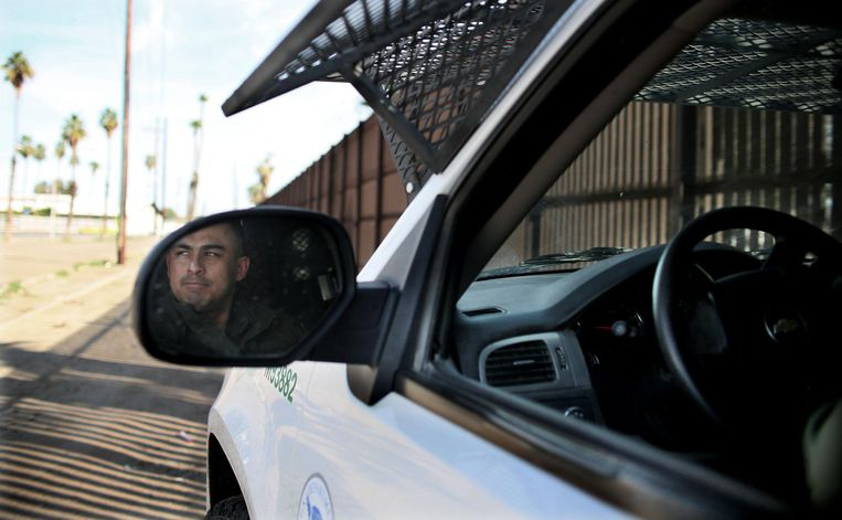 Een grenswacht kijk uit over de Mexicaanse grens bij Calexico. Beeld afp