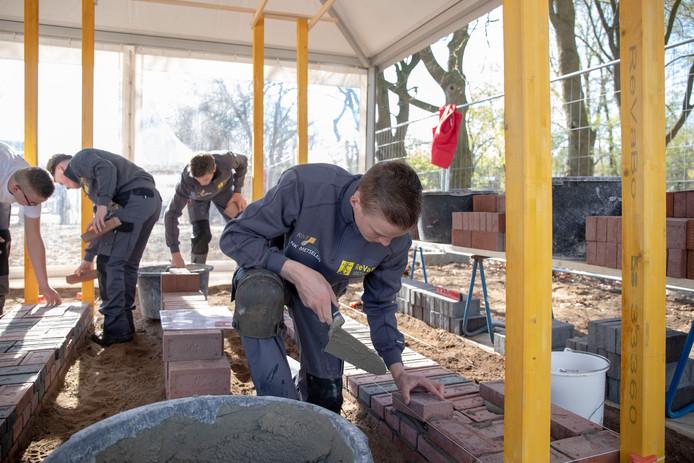 Geconcentreerd werkt een deelnemer aan het Nederlands kampioenschap metselen aan zijn meesterwerk.