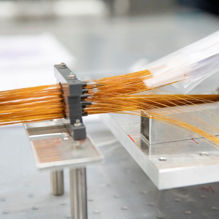Op haar werktafel vlecht astronoom Ellen Schallig ruim zeshonderd glasvezelkabels in elkaar. De labels aan het uiteinde geven aan waar welke kabel precies terecht moet komen in het uiteindelijke weefwerk.  Beeld Harry Cock/de Volkskrant