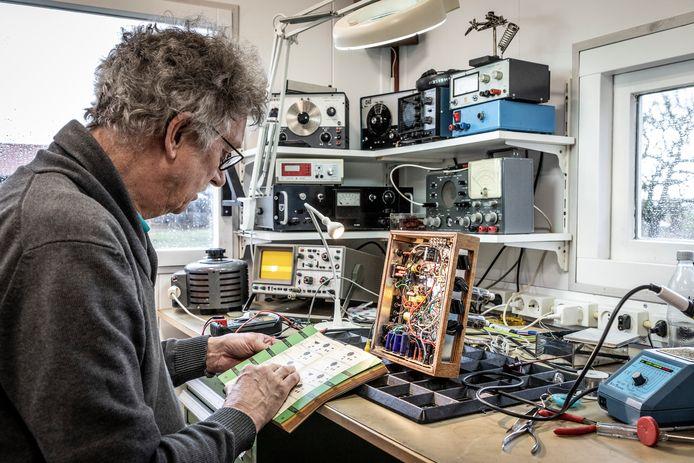 Fons Vendrik uit Ter Aar in zijn elektronicawerkplaats, geportretteerd in het boek 'Man & Werkplaats'