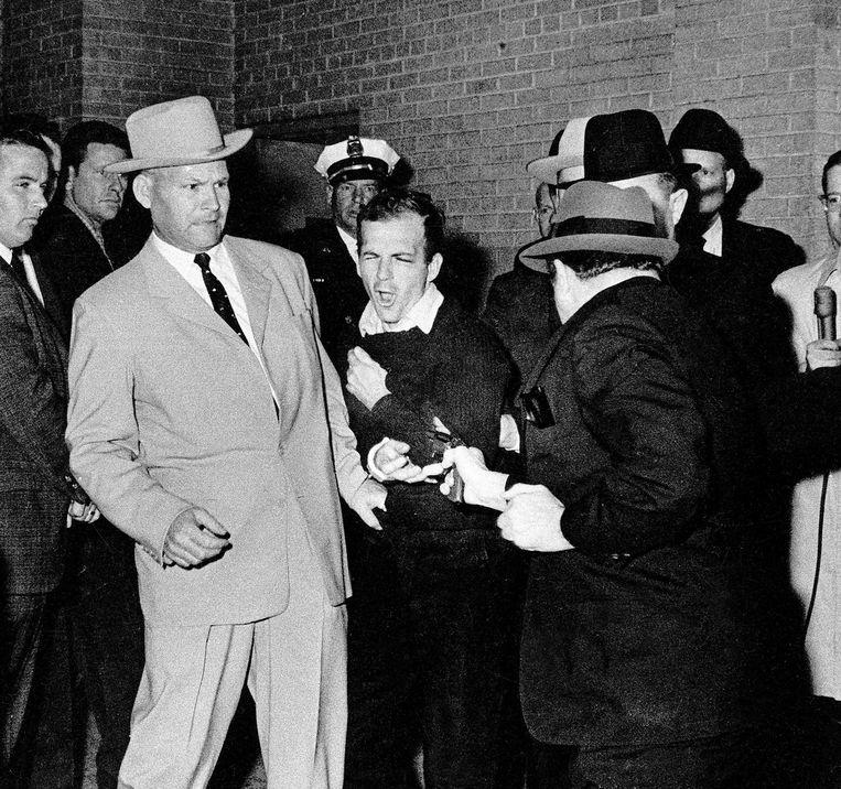 Jim Leavelle  (links) begeleidt Lee Harvey Oswald en ziet tot zijn ontzetting hoe Jack Ruby een revolvert trekt en vuurt.