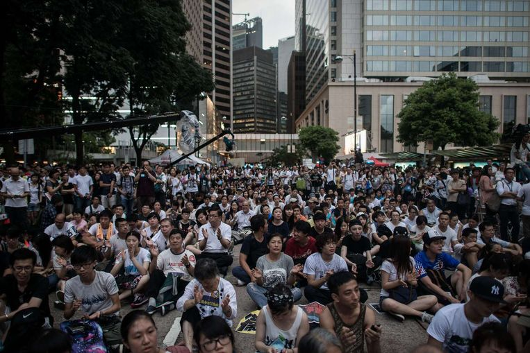 Demonstranten zitten op straat in een centraal gelegen gebied in Hongkong. Beeld afp