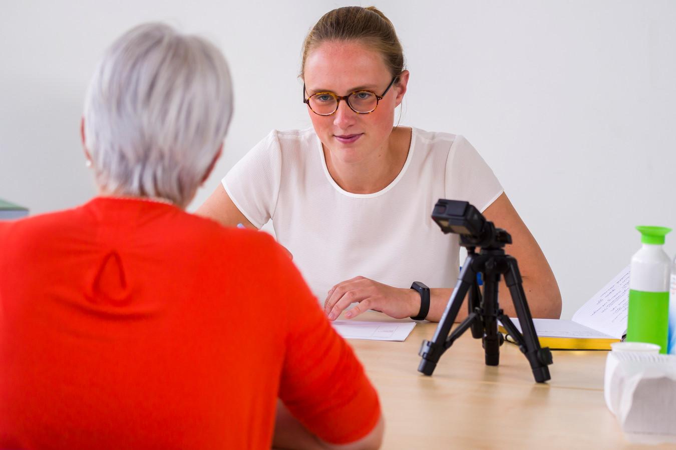 Onderzoekster Maud Schreijer van de Universiteit Twente laat Annemarie de coronameldapp testen.