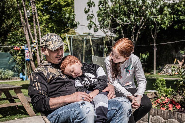 Amirouche Hammar met twee van zijn kinderen in de tuin van zijn huis in  Bobigny. Beeld Joris Van Gennip