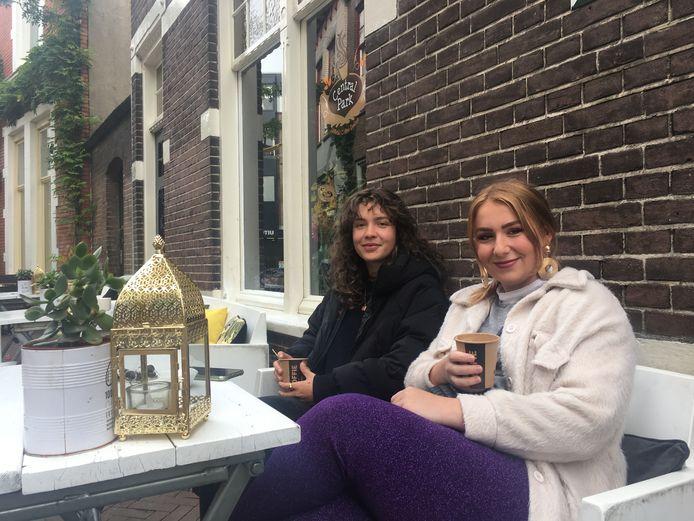 Jazz Diks (r) en Emma van Dieten pakken op de laatste dag dat het voorlopig kan een kop koffie op het terras van Central Park in Apeldoorn.