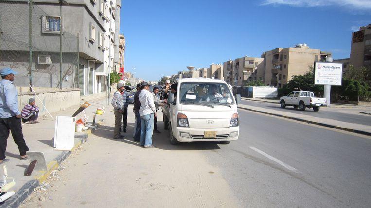 Dagloners wachten in Tripoli langs de weg in de hoop opgepikt te worden voor een klus. Beeld Marijn Kruk