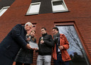 Wethouders Frans Stienen (links) en Paul Smeulders overhandigen het huisnummerbordje aan Emmelie en Rens.