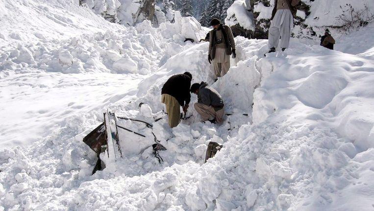 Reddingswerkers proberen een auto uit de sneeuw te graven na een sneeuwstorm in 2010 in Afghanistan. Beeld epa