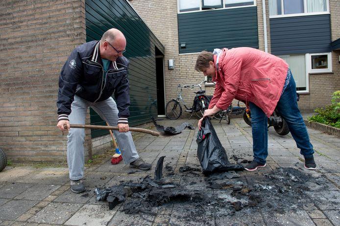 Maurits van Loenen en Sabrina van Herpen ruimen de rotzooi op. Hun door brand verwoeste auto is reeds afgevoerd.