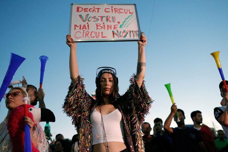 Een demonstrant tegen de regering houdt zondag in Boekarest een bord omhoog met de tekst: 'Beter ons circus, dan jullie circus'. Beeld EPA
