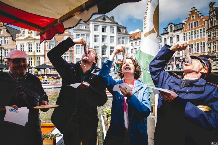 De burgemeester, schepen en belleman proeven de eerste Hollandse maatjes van het nieuwe seizoen.
