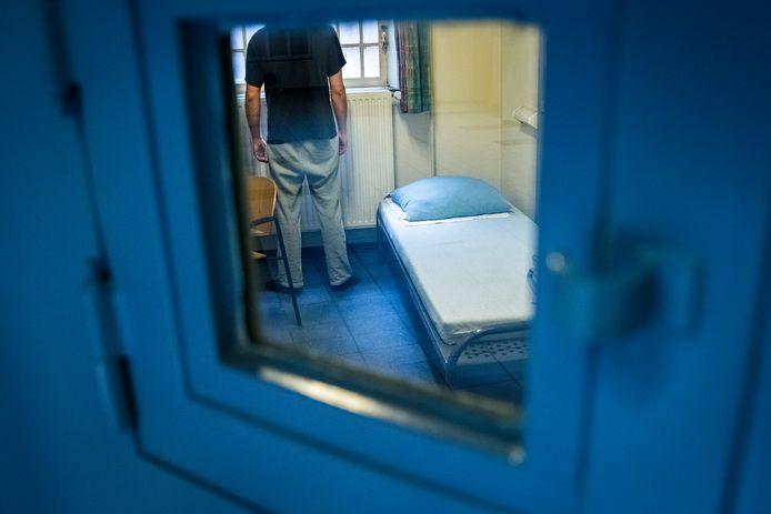 Ter illustratie:  Een man kijkt uit het raam van een cel in een gevangenis.