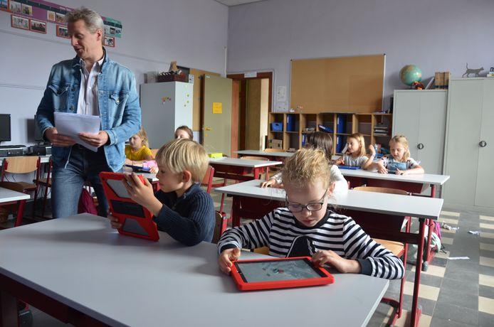 De kinderen gaan aan de slag met een tablet.