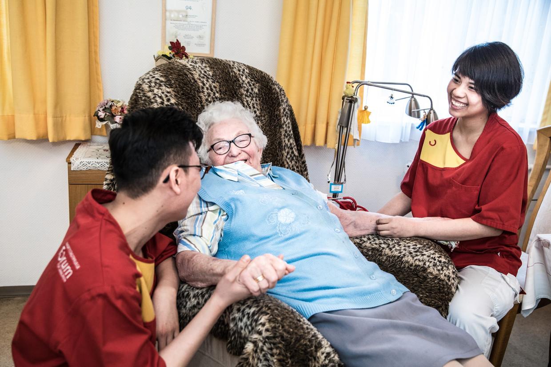 Hinh Thi Le (rechts) en Huy Pham (links) uit Vietnam met Mevrouw Belde in verpleeghuis Louise Schroeder in Berlijn. Beeld Waldthausen Marlena