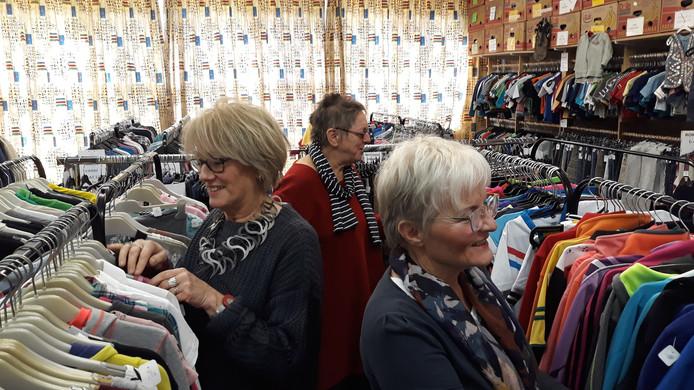 Anbertien Donders (op de achtergrond) hangt samen met Rina Kersbergen (links voor) en Ans Janssen tweedehands kleding aan de rekken. De kledingbank ruilt de klaslokalen aan de Irenestraat in voor de kantine van het voormalige SCI-complex.