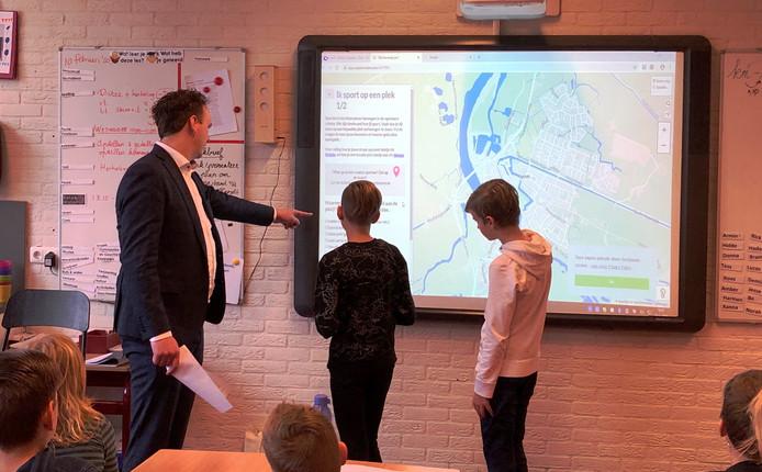 Op de De Driemaster vullen twee leerlingen de enquête in, geholpen door wethouder Maarten Slingerland.