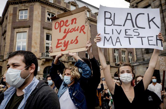 Beeld van het protest in Amsterdam, waar deelnemers mondkapjes droegen maar veel te dicht bij elkaar stonden.