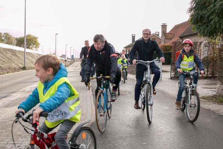 Minister Ben Weyts en burgemeester Luc De Ryck rijden met de kinderen van de plaatselijke basisschool op de nieuwe fietspaden langs de N41.