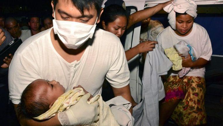Een hulpverlener ontfermt zich over een vrouw en haar baby nadat zij eerder gered waren van de veerboot. Beeld afp