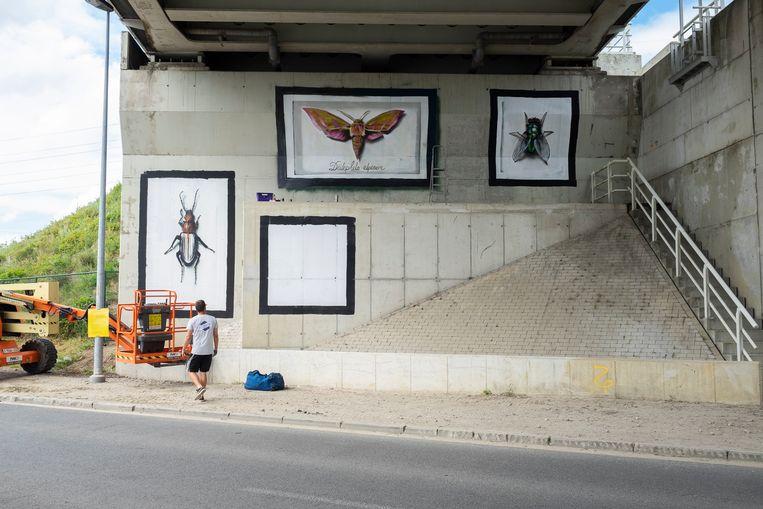 Een artiest werkt aan  een graffitiwerk langs de Vaartkaai ter ere van Julie Van Espen.