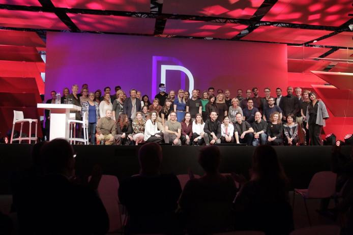 De 21 talentvolle designers samen met coaches op het podium.