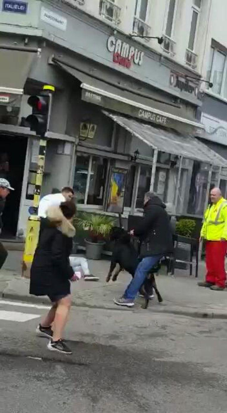 Slachtoffer K. (in witte broek) ligt op de grond, terwijl de hond in bedwang wordt gehouden.