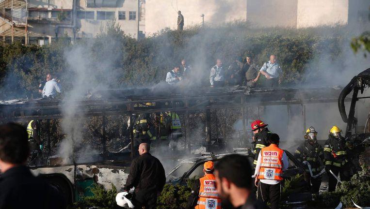 Hulpdiensten bij de uitgebrande bus. Beeld afp