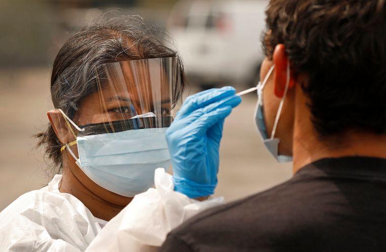 Een verpleegster neemt een coronatest af.