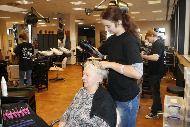 Een leerling brusht het haar van haar grootmoeder.