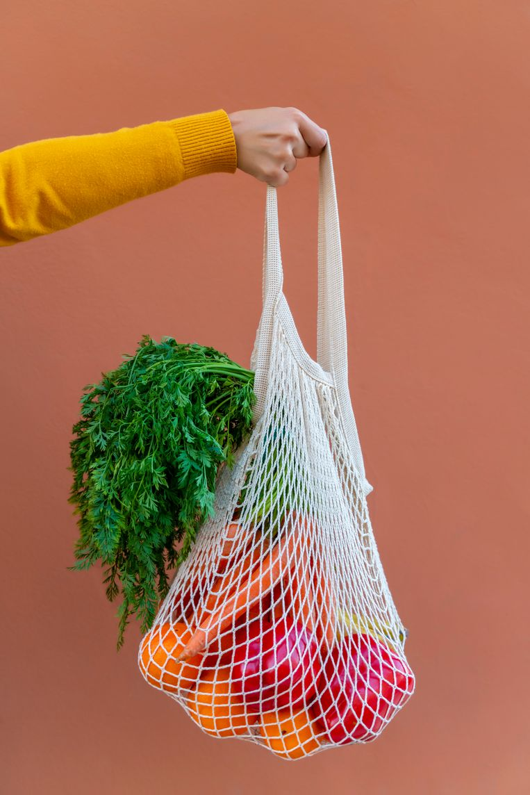Cropped woman hand holding ecologically friendly reusable cotton mesh bag with fruit and vegetables. Zero Waste shopping concept. Salmon color background. boodschappen tas Beeld Getty Images