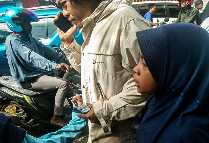 Een man begeleidt kinderen een schoolgebouw uit nadat de aardbeving Ambon trof.
