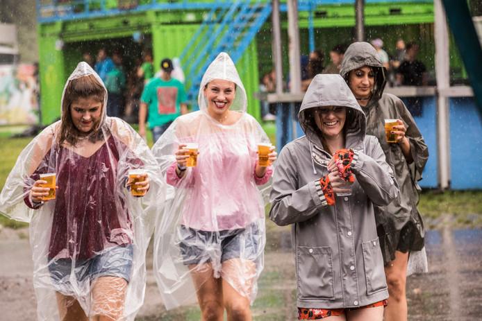 Deze vrouwen kunnen nog lachen tijdens een fikse regenbui op Lowlands 2017. Maar festivalorganisatoren in Twente willen dit soort taferelen voor zijn.