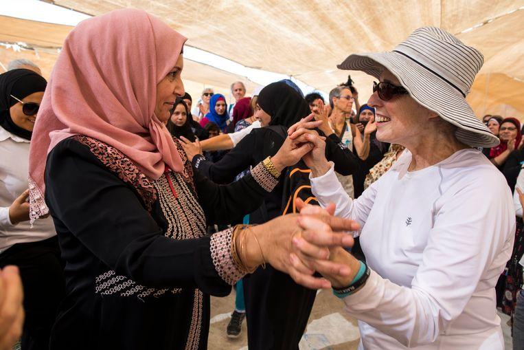 Palestijnse en Israëlische vrouwen dansen, begin deze maand, met elkaar tijdens een protestmars op de Westelijke Jordaan-oever. Ze willen dat er een eind komt aan het Palestijns-Israëlisch conflict.  Beeld EPA