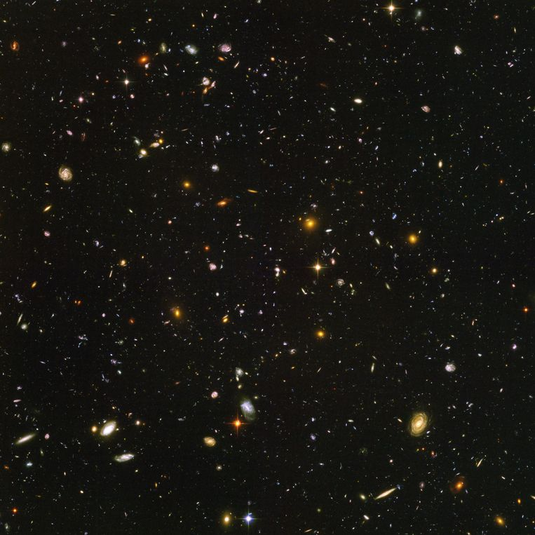 Een minuscuul stukje hemel bevat al duizelingwekkend veel sterrenstelsels, op deze foto in totaal zo'n 10 duizend. De vaagste rode puntjes die u hier ziet zijn enkele van de verst bekende stelsels. U ziet ze zoals ze er slechts 800 miljoen jaar na de geboorte van het heelal bij stonden. De grotere, heldere stelsels op de voorgrond werden pas geboren toen het heelal al 13 miljard jaar oud was. Beeld Nasa & Esa