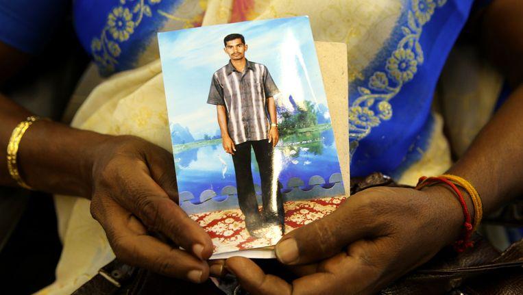 Een Tamil-vrouw behorend tot de etnische minderheid in Sri Lanka houdt een foto van haar vermiste zoon vast Beeld getty