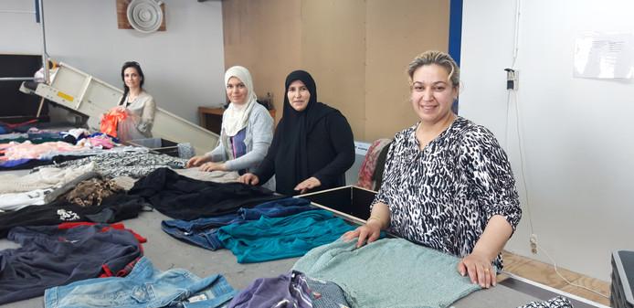 Statushouders uit Almelo werken als vrijwilliger in het kledingsorteercentrum van kringloopbedrijf De Beurs in Tubbergen, met Fatima al Kalzi (tweede van links) en Bahisa Aebed (rechts)  met collega's aan de sorteerband.