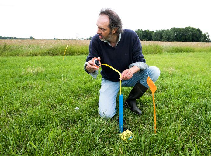 Rene Faber meet op het gehoor het grondwaterpeil op het weiland van boer Blonk  (Foto Marnix Schmidt)
