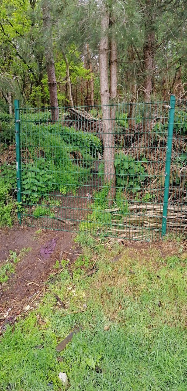 Het hek dat leidt naar de homo-ontmoetingsplaats in het bos bij Riel is afgesloten