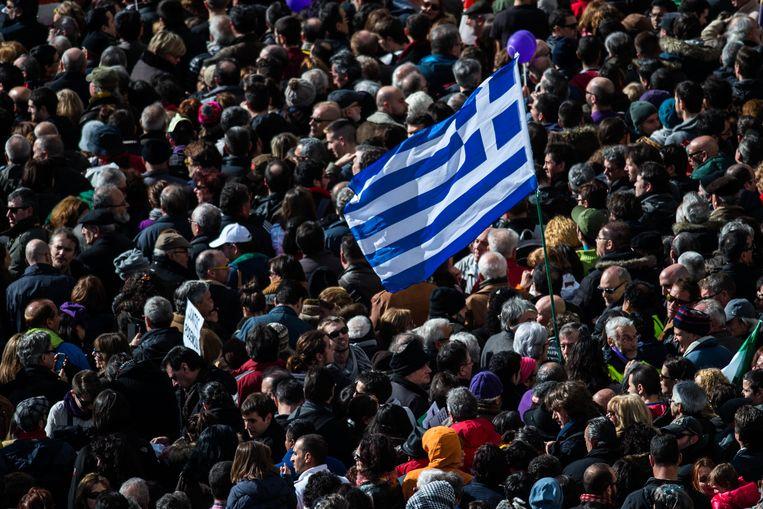 Demonstranten in Madrid zwaaien met een Griekse vlag Beeld getty
