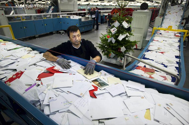 Een postmedewerker sorteert kerstkaarten en andere post bij het sorteercentrum in Amsterdam.  Beeld ANP