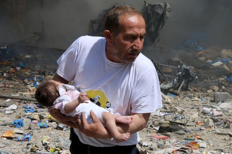 Een man met een baby die het bombardement op Aleppo overleefde. Activisten zeggen dat het Syrische regeringsleger de stad bombardeerde. Beeld null