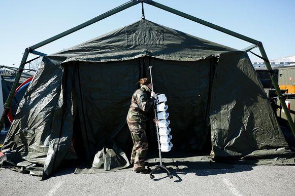 Franse militairen hebben op de parking van een ziekenhuis in Mulhouse een veldhospitaal opgetrokken. Het gewone ziekenhuis kan de toevloed van coronapatiënten niet meer aan.