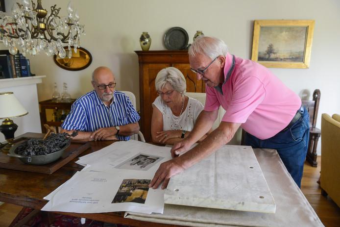 Peter Bakker (rechts) bekijkt de drukproeven samen met Ben van Damme en Mart Meeske. Voor hem ligt de gerestaureerde eerste steen van de Ontmoetingskerk. Op de kop, want het opschrift wordt pas bij de onthulling op 11 september weer getoond.