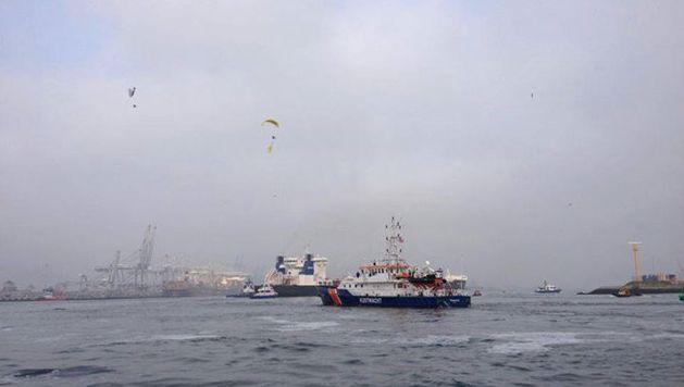 Paragliders van Greenpeace boven de Russische olietanker (m) in de haven van Rotterdam met op de voorgrond een schip van de kustwacht.