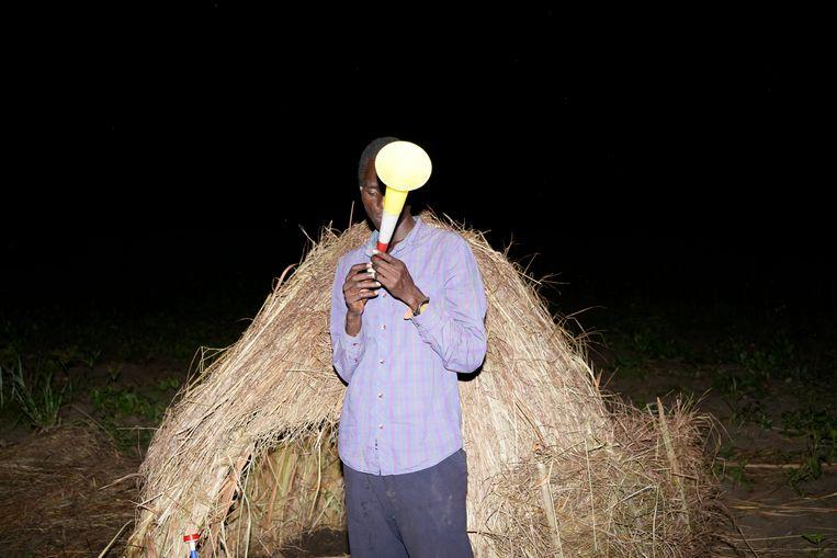 Nelson Okello (28) met de vuvuzela waarmee hij de olifanten wegjaagt die anders zijn sojagewassen opeten. Beeld Michele Sibiloni