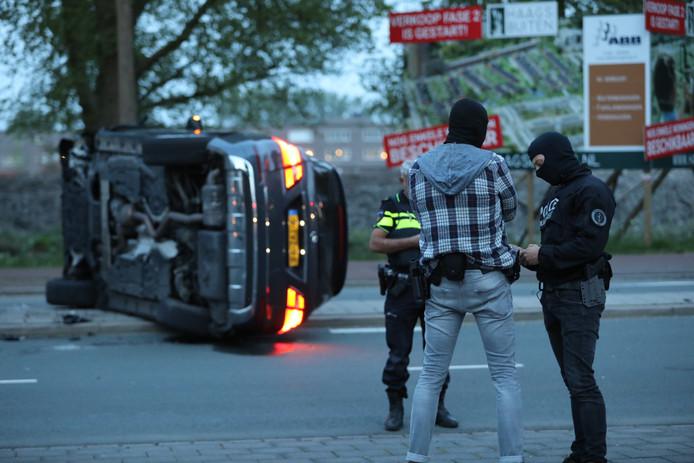 Arrestatiebusje op z'n kant op Erasmusweg na achtervolging.