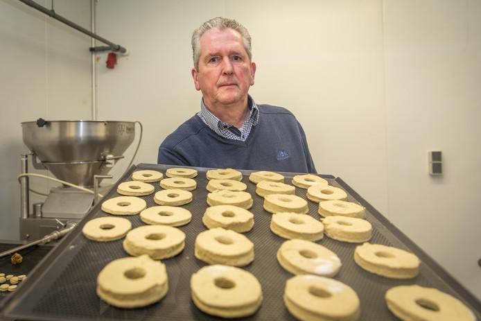 Cor Poppe met een blik donuts waarin visvlees van mesheften is verwerkt. Ze moeten nog de oven in.