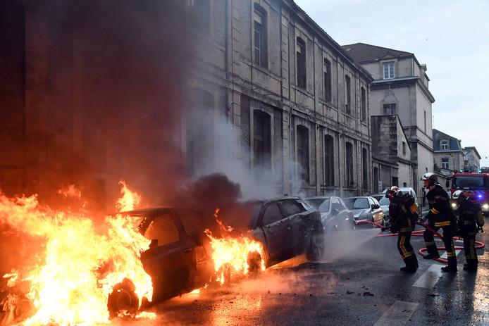 Brandweermannen blussen brandende auto's tijdens de 13e protestdag van de Gele Hesjes