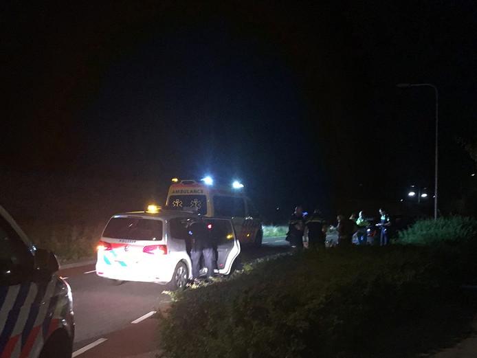 Politie-agenten bekijken de schade aan de geramde voertuigen.
